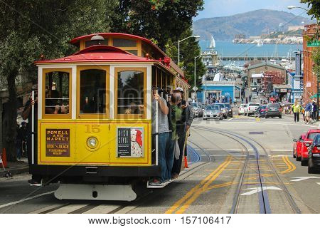 San Francisco California - Mai 23 2015: Lot Tourists riding on the iconic cable car blue sky day at top of Hyde Street view overlooking the bay water and Alcatraz prison