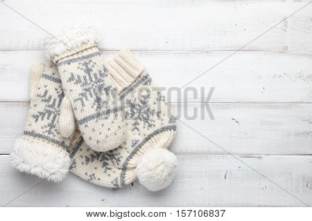 Winter background with knitted mittens and cap