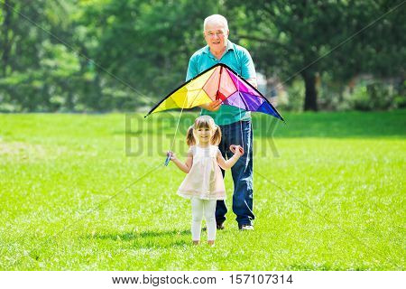 Happy Senior Grandfather Flying Kite In Park With His Smiling Granddaughter