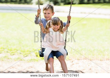 Two Happy Children Enjoying On Swing In The Park