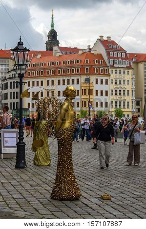 DRESDEN GERMANY- JULY 13 2015: a performer - Golden painted artists on a city street living statues