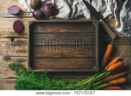 Healthy food cooking background. Vegetable ingredients. Fresh garden carrots and beetroots on rustic wooden background with wooden tray in center, top view, copy space, horizontal composition