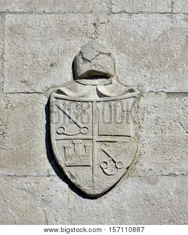 Religious stone emblem of bishop with keys and castle symbols on Saint Peter church bell tower in Venice