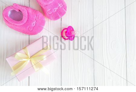 baby's bootees and gift box on wooden background top view