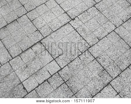 Decorative colorful sidewalk pavement. Tiled floor with grey tiles crossed by a diagonal double stripe of red tiles viewed at a low angle full frame background pattern
