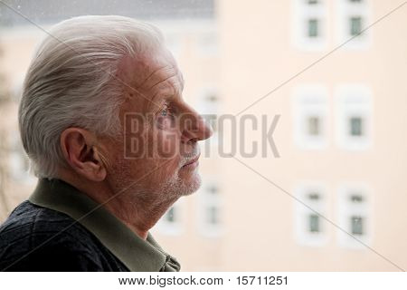 Senior stands sadly in window