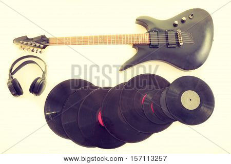 Equipment of musician. Electric electro black guitar string intrument big headphones and vinyl records lying ready to use.
