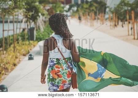 Rear view of curly brazilian girl with small bag and waving flag of Brazil on summer day in Rio de Janeiro