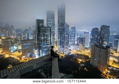 HONG KONG, CHINA - JAN 30, 2016: Man sits on roof of tall building in city. Hong Kong is one of largest business centers in Asia and around world, it has built more than 1.3 thousand skyscrapers