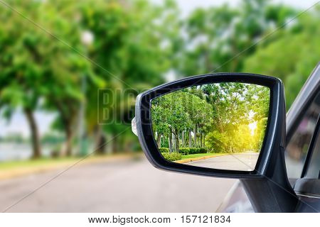side rear-view mirror on a car on the road.