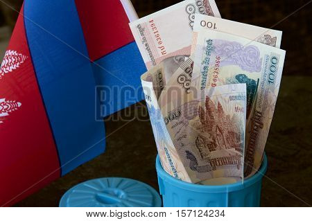 Cambodia riel notes and flag in a blue garbage bin.