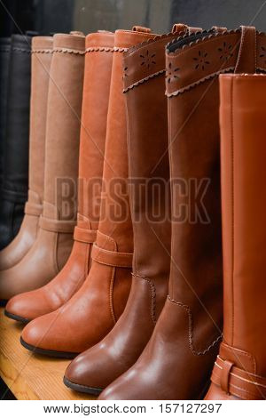 row of women's boots shoes on wooden shelf