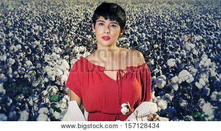 Fashion art concert image.  Beautiful woman looking to side profile shot, wearing red dress in cotton field.  Image cross processed/