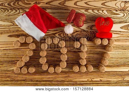 Inscription 2017 laid out champagne corks, two red hearts with the word LOVE and a cap of Santa Claus on a wooden table for background. New Year.