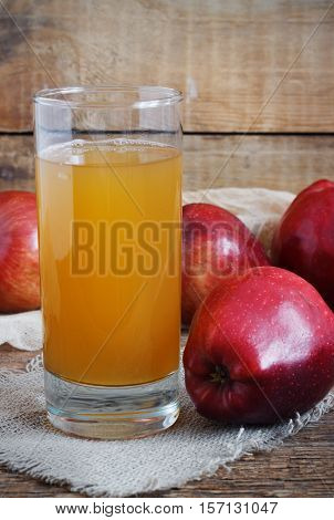 Glass of apple juice and red apples on old wooden background