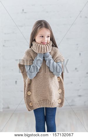 Fashion child knitted sweater in the Studio. The child in a warm jacket.