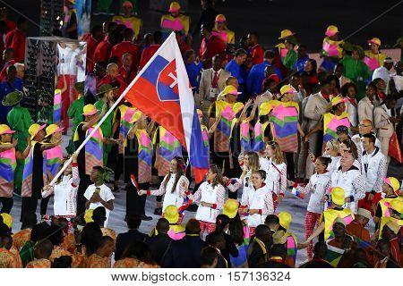 RIO DE JANEIRO, BRAZIL - AUGUST 5, 2016: Skeet shooter Danka Bartekova carrying the Slovakian flag leading the Olympic team Slovakia during the Rio 2016 Opening Ceremony at Maracana Stadium