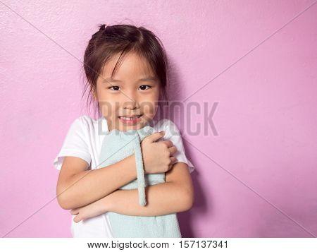 portrait of a little asian kid girl hug her bolster