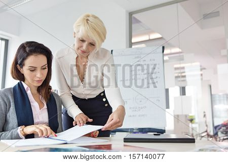 Mature businesswoman with female colleague reviewing project at desk in office
