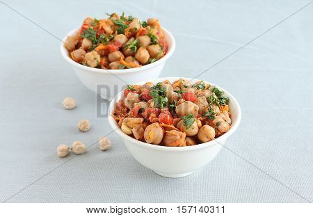 Indian vegetarian food channa chat, also known as chickpea or garbanzo curry, is eaten as a snack or is used as a side dish, in two bowls.