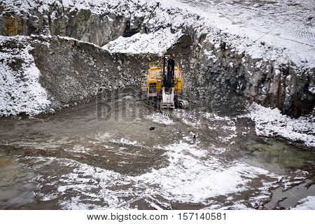 big huge yellow excavator in a granite quarry in winter. huge loading shovel bucket stands on a granite floor strewn with snow in his career on a winter day