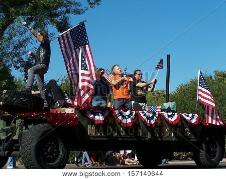 PHOENIX, AZ- NOV. 11: Group Madison Rising on float decorated with flags at the Veteran's Day Parade in Phoenix, Arizona on November 11, 2013.