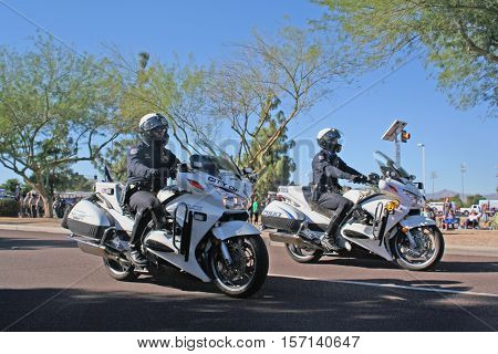 PHOENIX, AZ- NOV. 11: Two male police officers wearing helmets riding motorcycles in the Veteran's Day Parade in Surprise, Arizona on November 11, 2016.