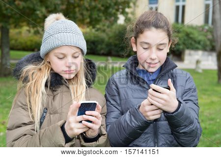 Euphoric friends watching videos on a smartphone outdoors