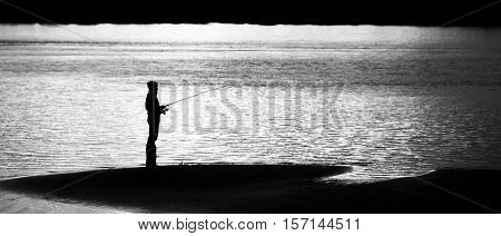 Fisherman With A Fishing Rod On The River Bank. Man In Warm Clothes And A Hood, Enthusiasm Catches F