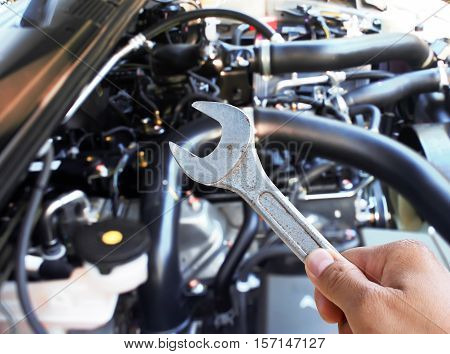 Hand with wrench checking car engine background.