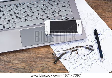 Minsk, Belarus - April 16, 2016: Business concept. Laptop Samsung Series 7 Ultra OS Windows 8.1, 10 and Apple iPhone 5S on table with documents, Sunglasses. Apple Inc. and Samsung Group.