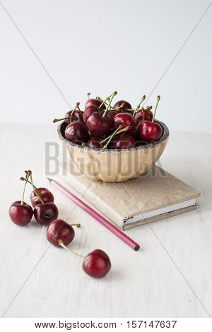 Juicy ripe sweet cherries lie on a white plate and wooden background