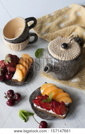Sandwiches With Sweet Cheese, Fruit And Berries, And Tea Cups On A White Wooden Background
