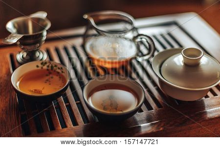 Chinese tea ceremony, shen puer tea, transparent glass, Pialats, tea set on a wooden table.