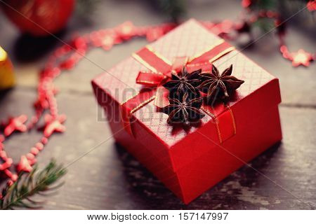 Gift box, anise and bijouterie on a wooden background