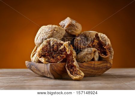 Dried Figs In Wooden Dish On Ceramic Table