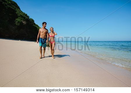 Full length shot of young honeymoon couple walking on the beach. Young man and woman strolling on the sea shore.