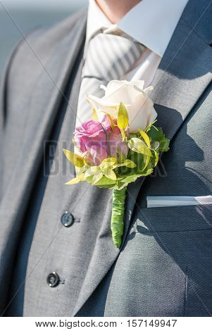 colorful corsage on the jacket of a young and handsome groom with a nice gray suit