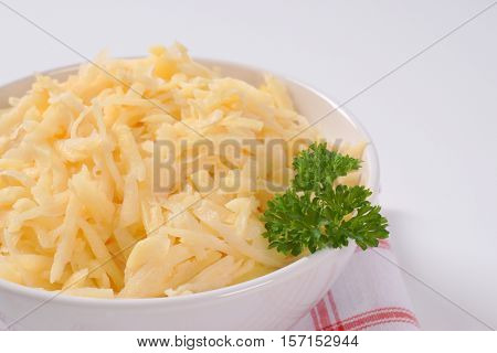 bowl of grated raw potatoes on checkered dishtowel - close up