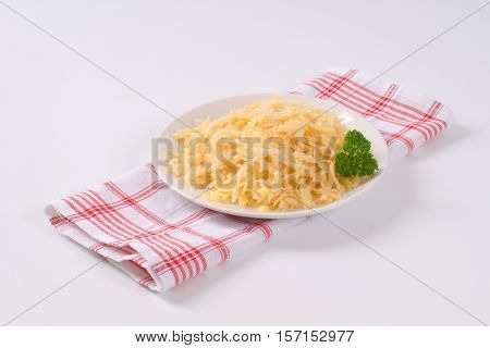 plate of grated raw potatoes on checkered dishtowel