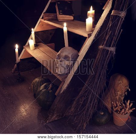 Scary still life with human skull, candles, broom and evil staircase in witch house. Occult or esoteric ritual with magic objects, Halloween background