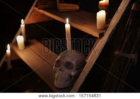 Mystic still life with skull and candles on wooden staircase. Occult or esoteric ritual with magic objects, scary Halloween background