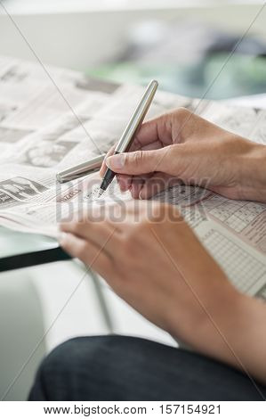 Woman making a crossword puzzle sitting on a table. Hand doing crossword