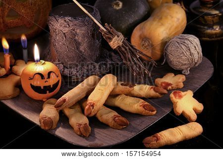 Halloween background with finger cookies and witch magic objects in candle light. Pumpkins, broom stick and warlock hat with traditional sweets