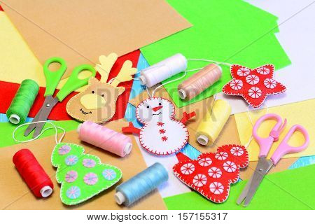 Cute Christmas tree ornaments crafts. Stuffed felt Christmas tree, star, snowman, deer diy, colored thread, felt sheets, needle, scissors. Christmas tree ornaments background. Kids winter sewing craft