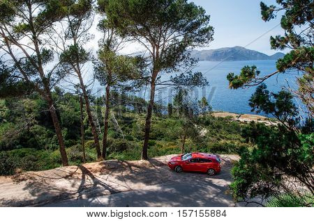 Alcudia Mallorca Spain - May 23 2016: Seascape of Mediterranean Sea with a red car Volvo V40 traveling on the mountain serpentine through the pine forest along the coast of Majorca. Auto travel concept