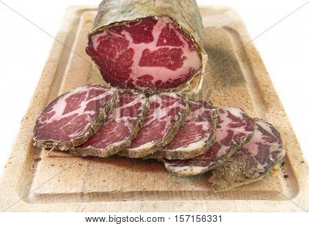 Capocollo and slice in front of white background