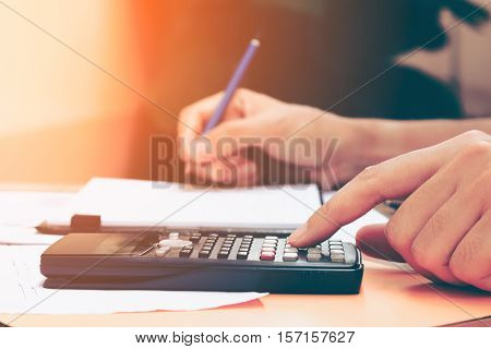 Close up young woman with calculator counting making notes at home hand is writes in a notebook. Savings finances concept.