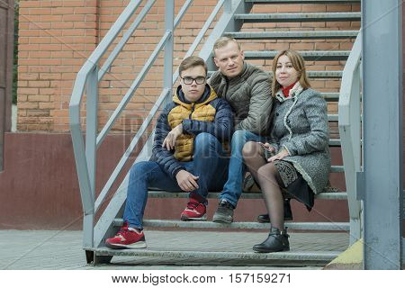 Family city street urban portrait are sitting on metal stairs at brick building background