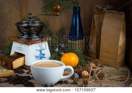 Coffee beans in the white ceramic cup and manual coffee mill on the wooden background